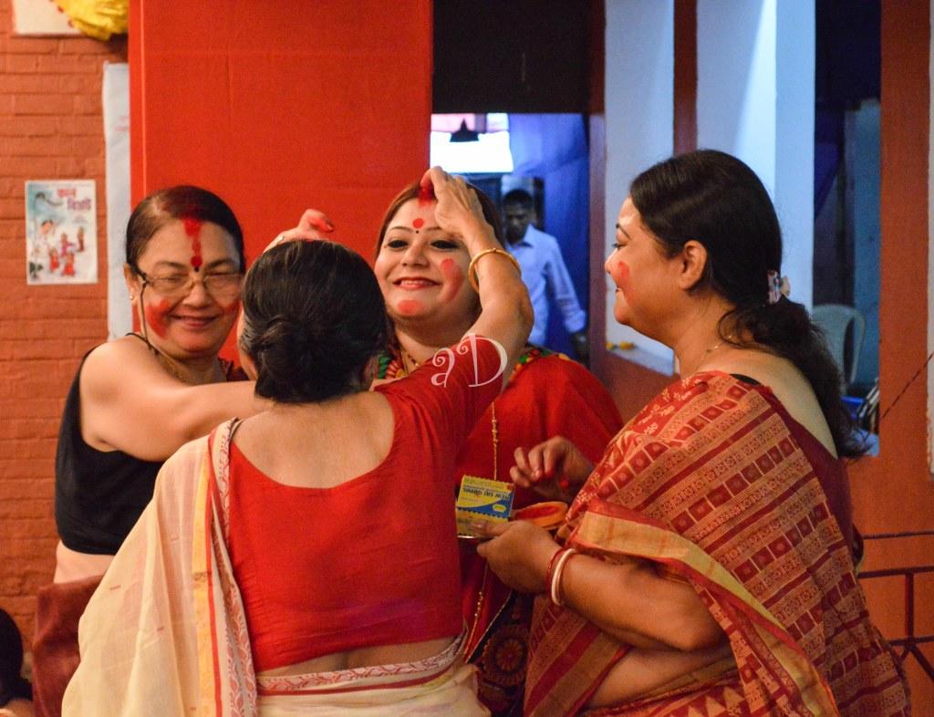 Women smear each other with Sidur (vermillion)