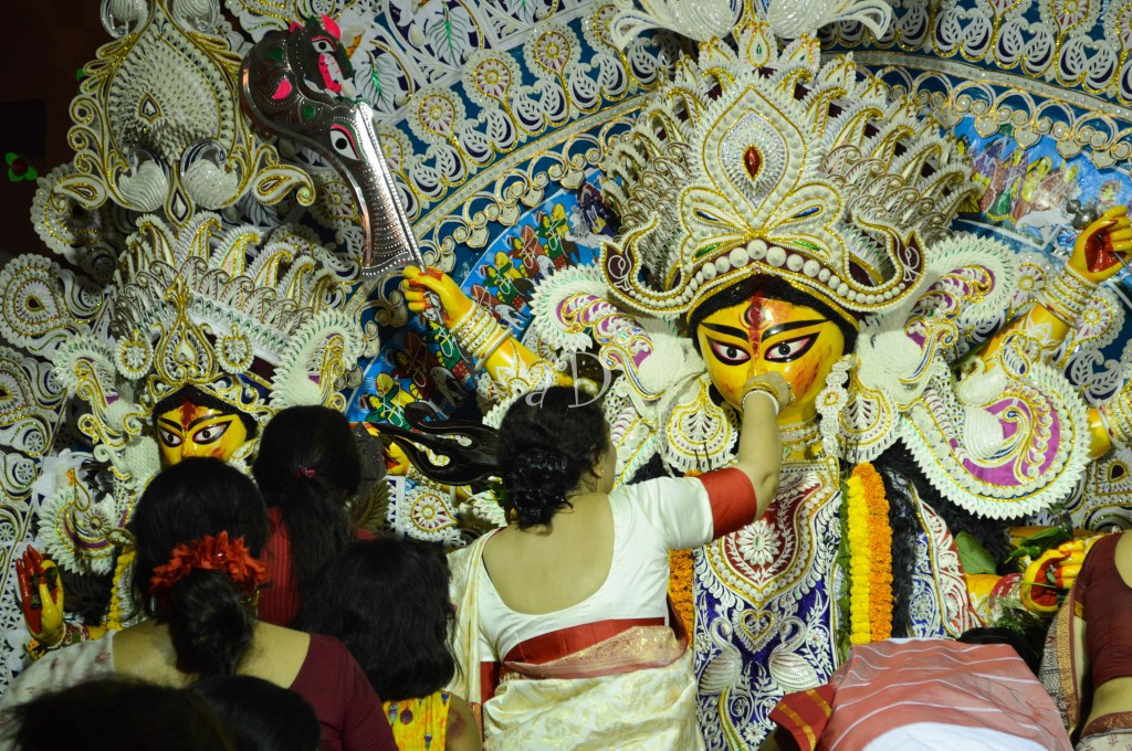 As every lal-paar sada sari clad bengali woman performs Durga Boron with utmost devotion